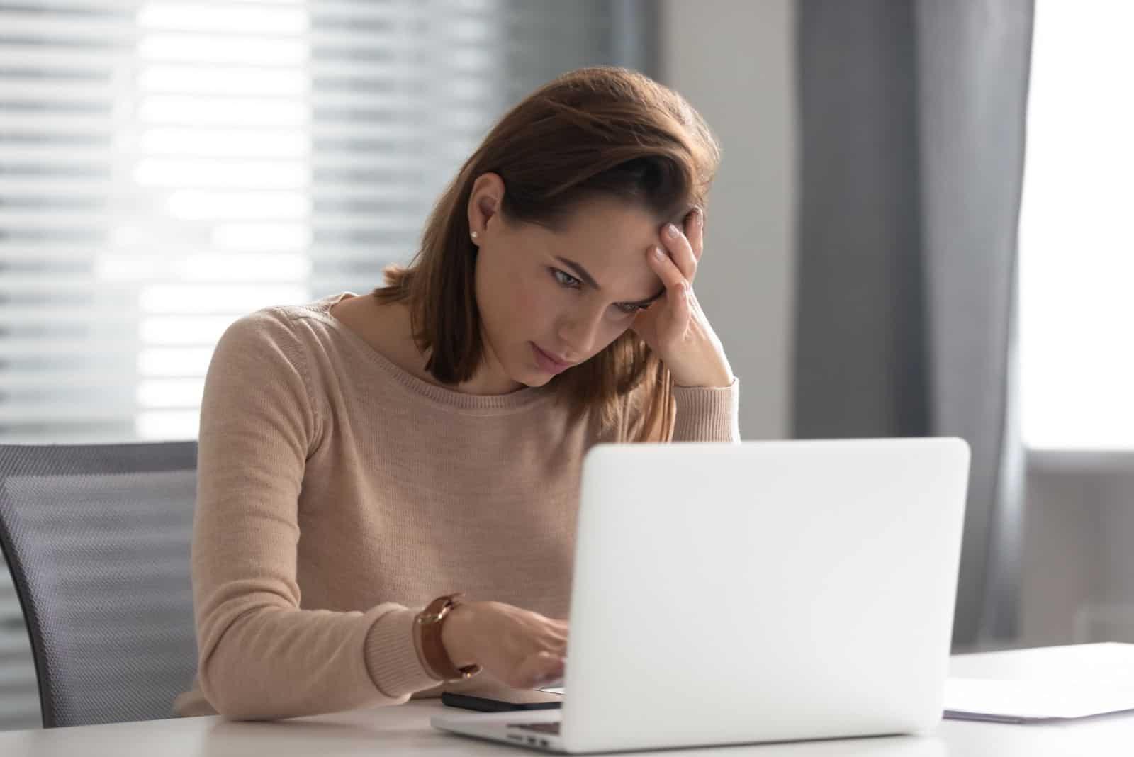 gestresste junge Geschäftsfrau mit Laptop-Top leiden Kopfschmerzen