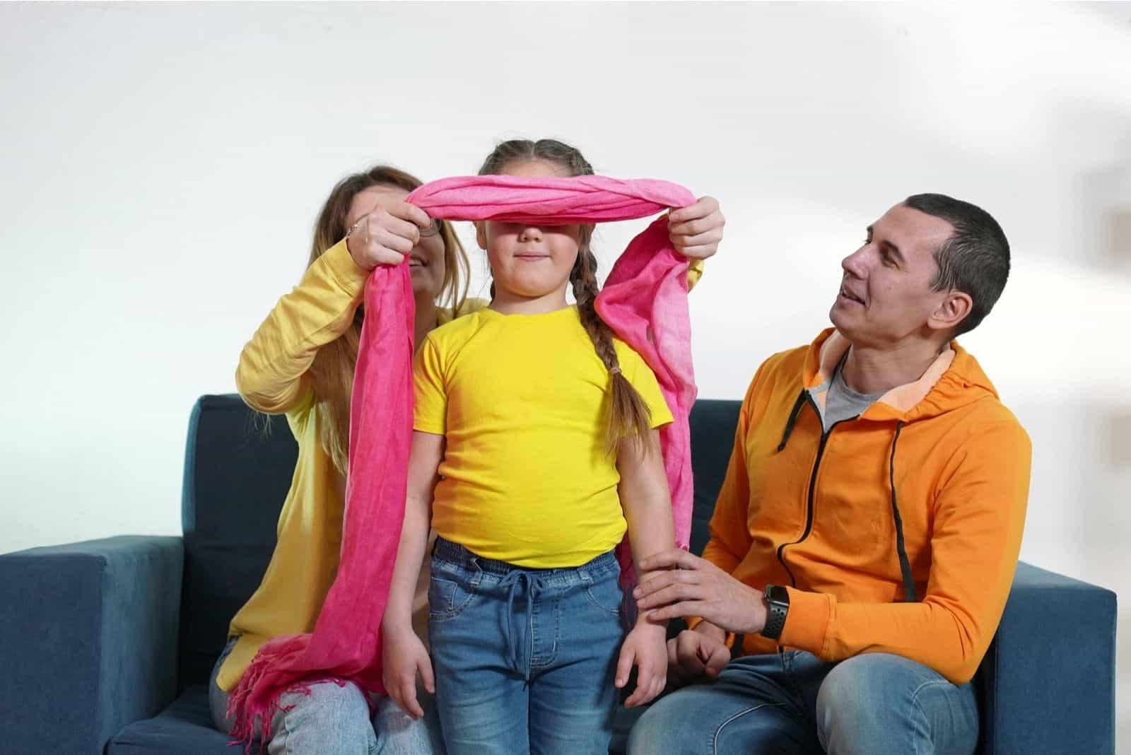 glückliche Familie zu Hause wenn Mama dem Kind eine Augenbinde auflegt