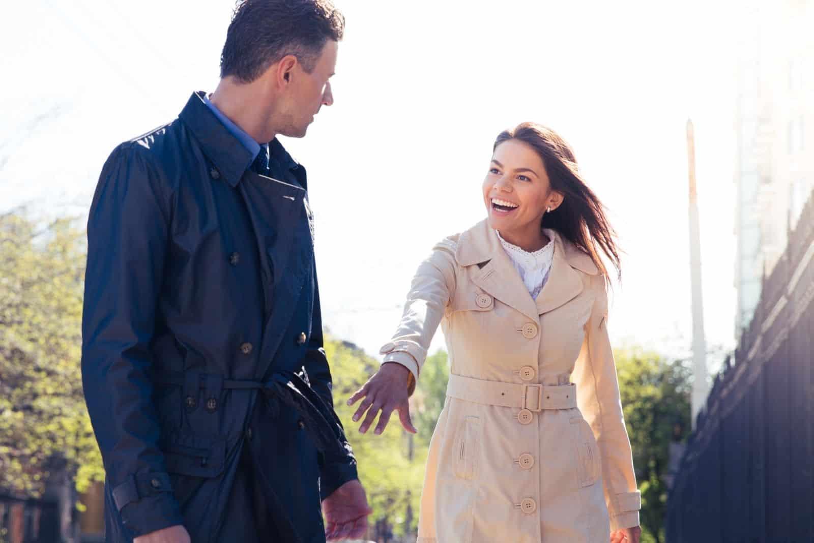 glückliche junge Frau, die Mann im Freien einlädt