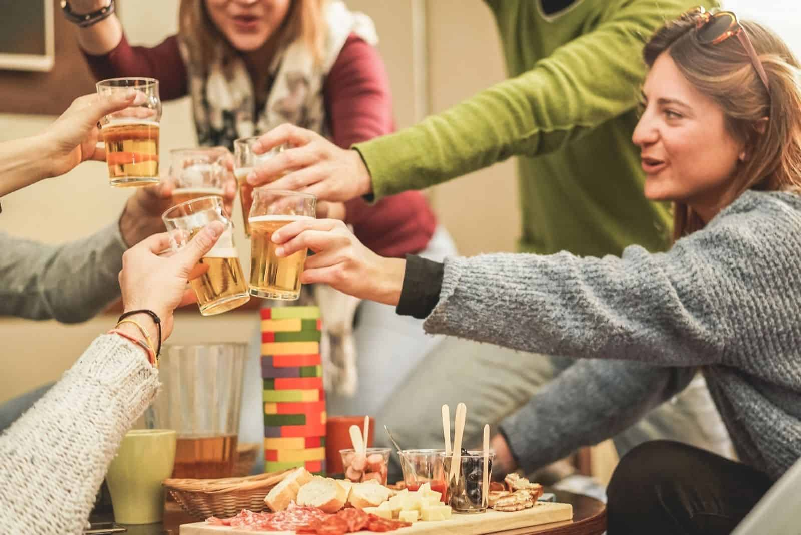 glückliche reiche Freunde Jenga-Spiel mit Bier in einer Brauerei-Chalet-Party spielen