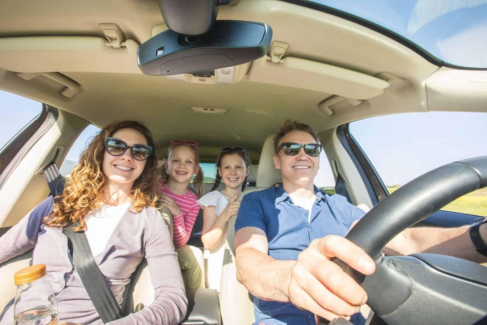 glückliche reisende Familie im Auto bei schönem Wetter