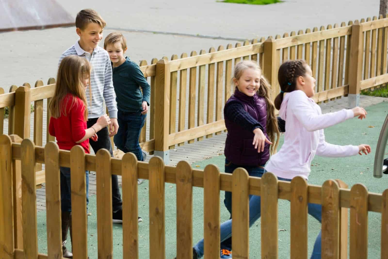 glückliche spielende Kinder innerhalb eines Zauns im Freien fangen und berühren