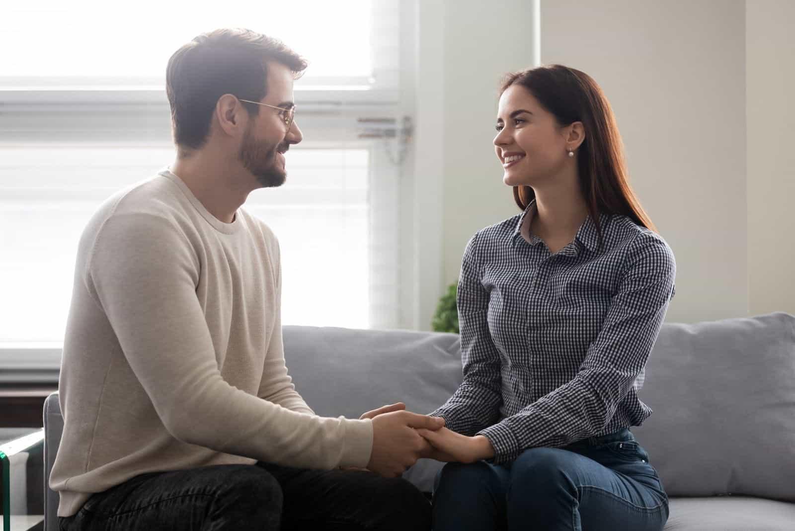 glücklicher junger Mann Händchenhalten der Frau im Wohnzimmer