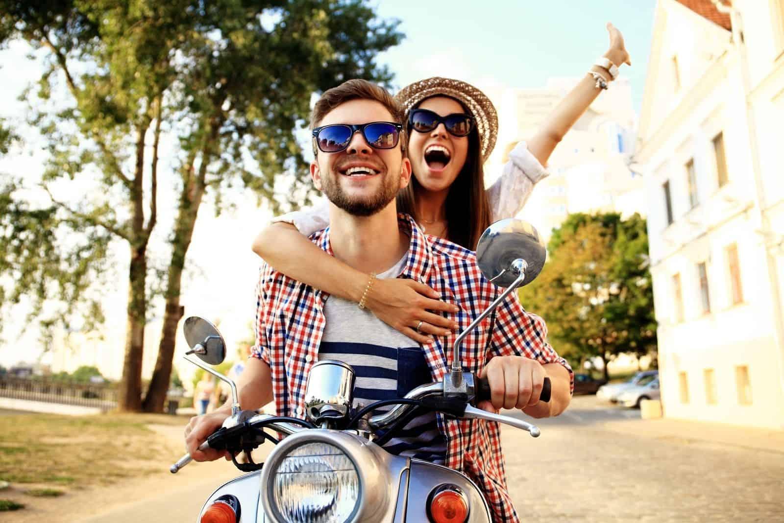 glückliches Paar Reiten ein Motorrad im Sommer