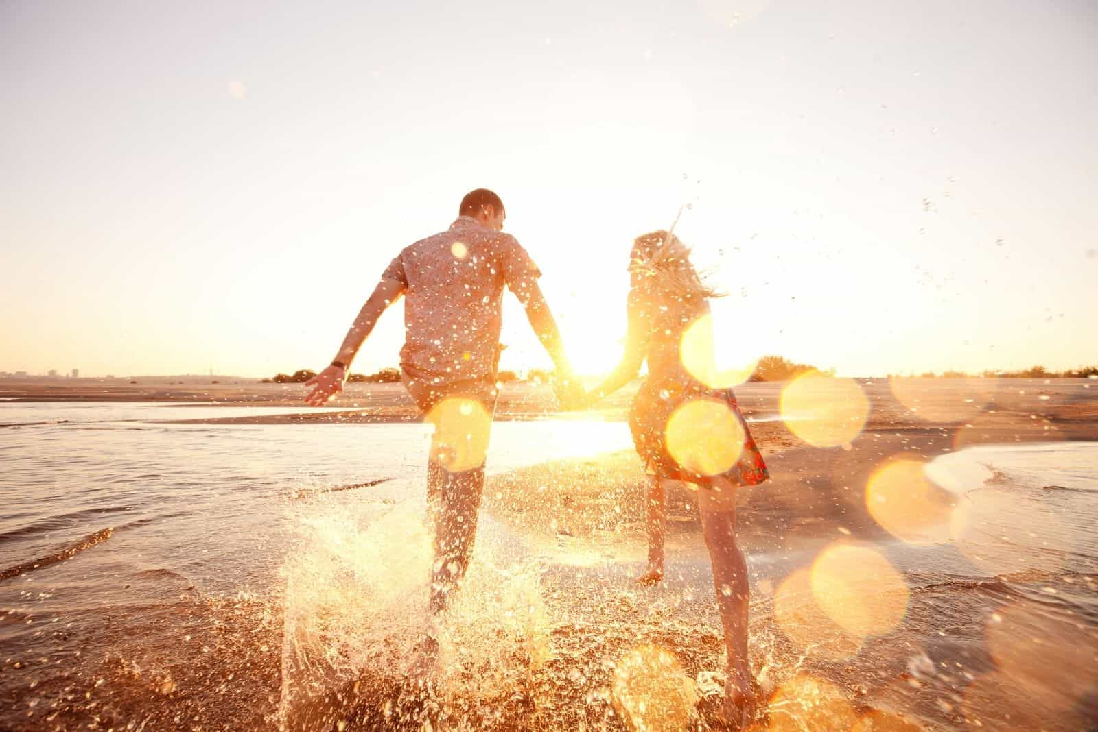 glückliches Paar läuft am Strand mit Blick auf die Sonne