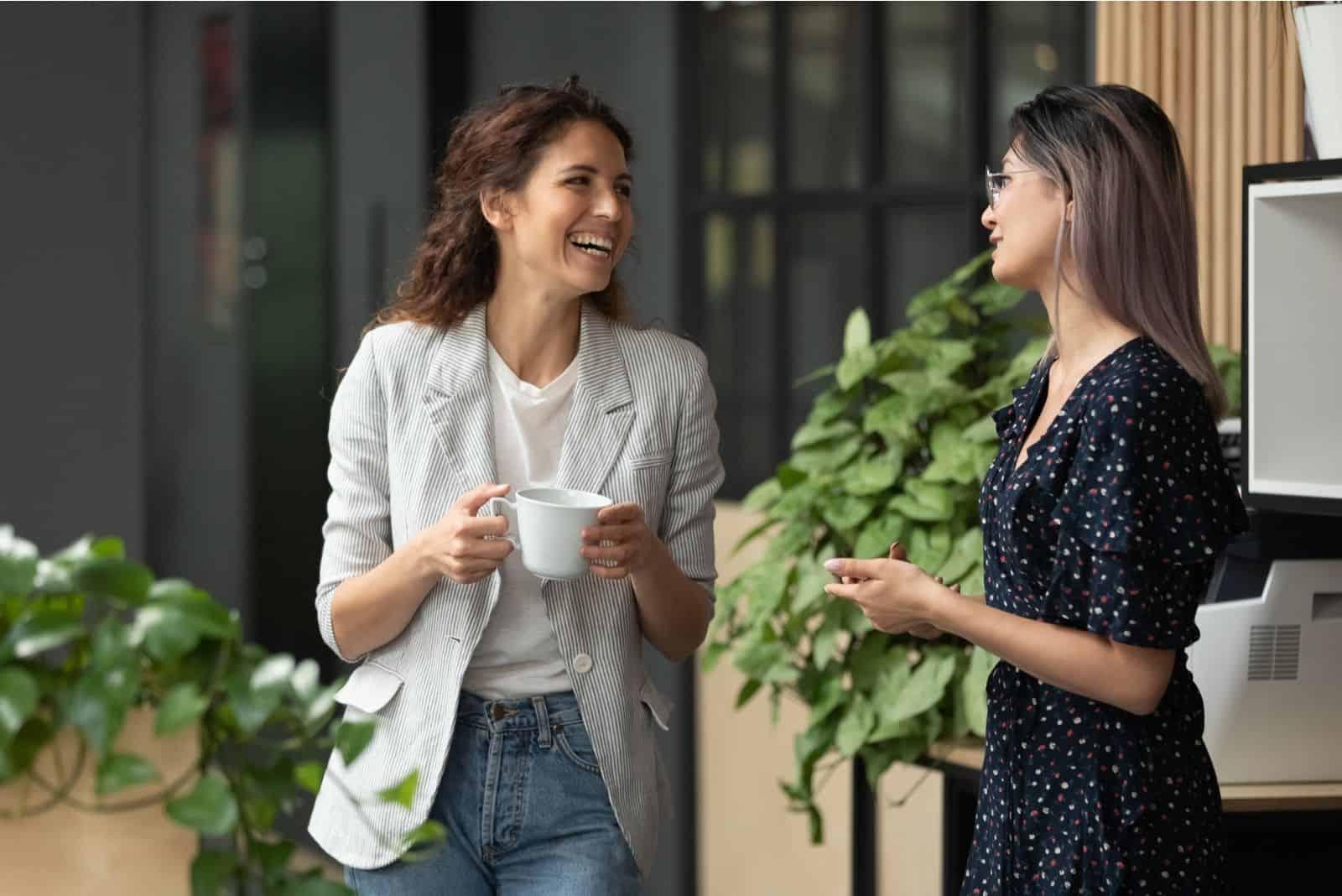 glückliches positives weibliches Lachen und Plaudern während der Kaffeepause