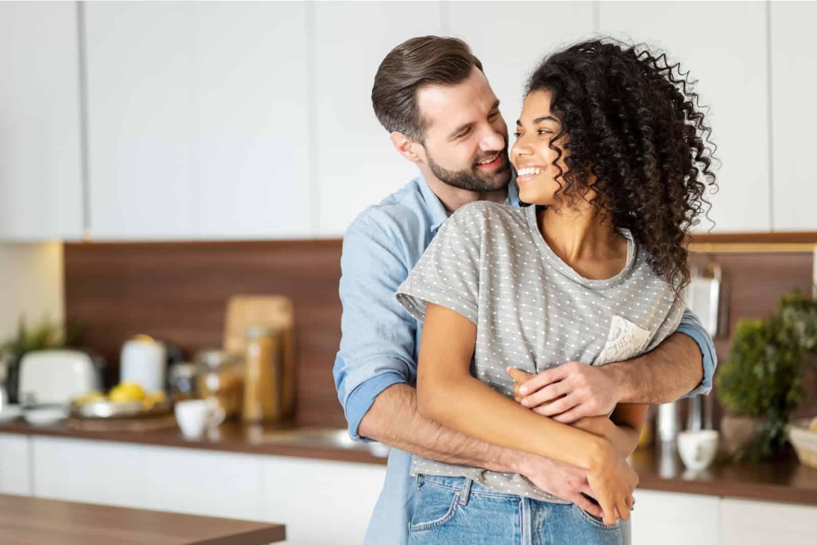 gut aussehender Mann, der seine Freundin in der Küche umarmt