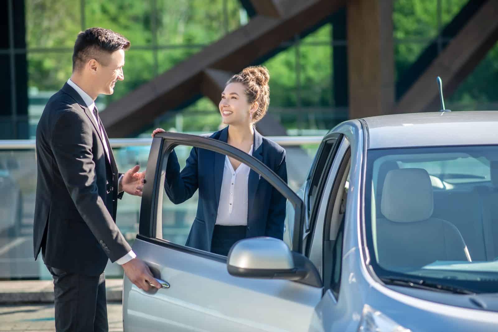 höflicher junger Mann Autotür einer Kollegin öffnen