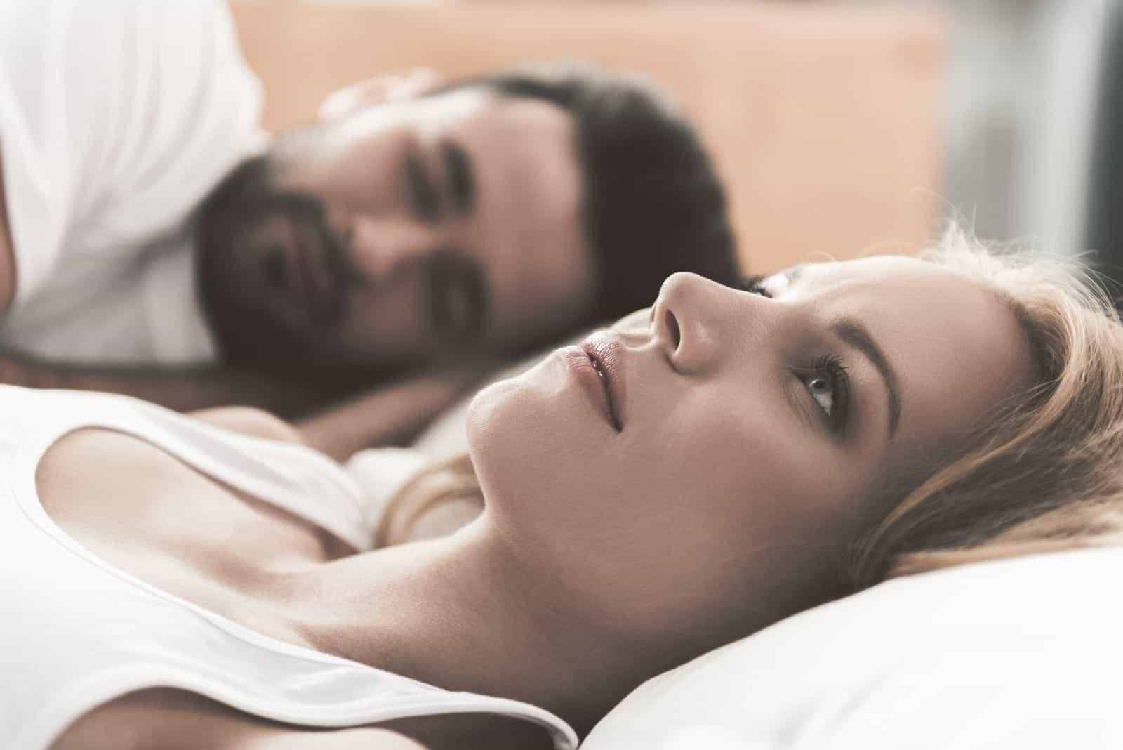 junge Frau macht sich Sorgen über ihre Ehe wach neben dem schlafenden Ehemann liegen