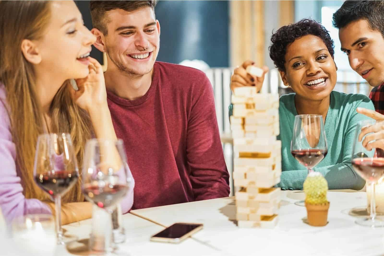 junge Freunde trinken Spiel mit Jenga-Spiel