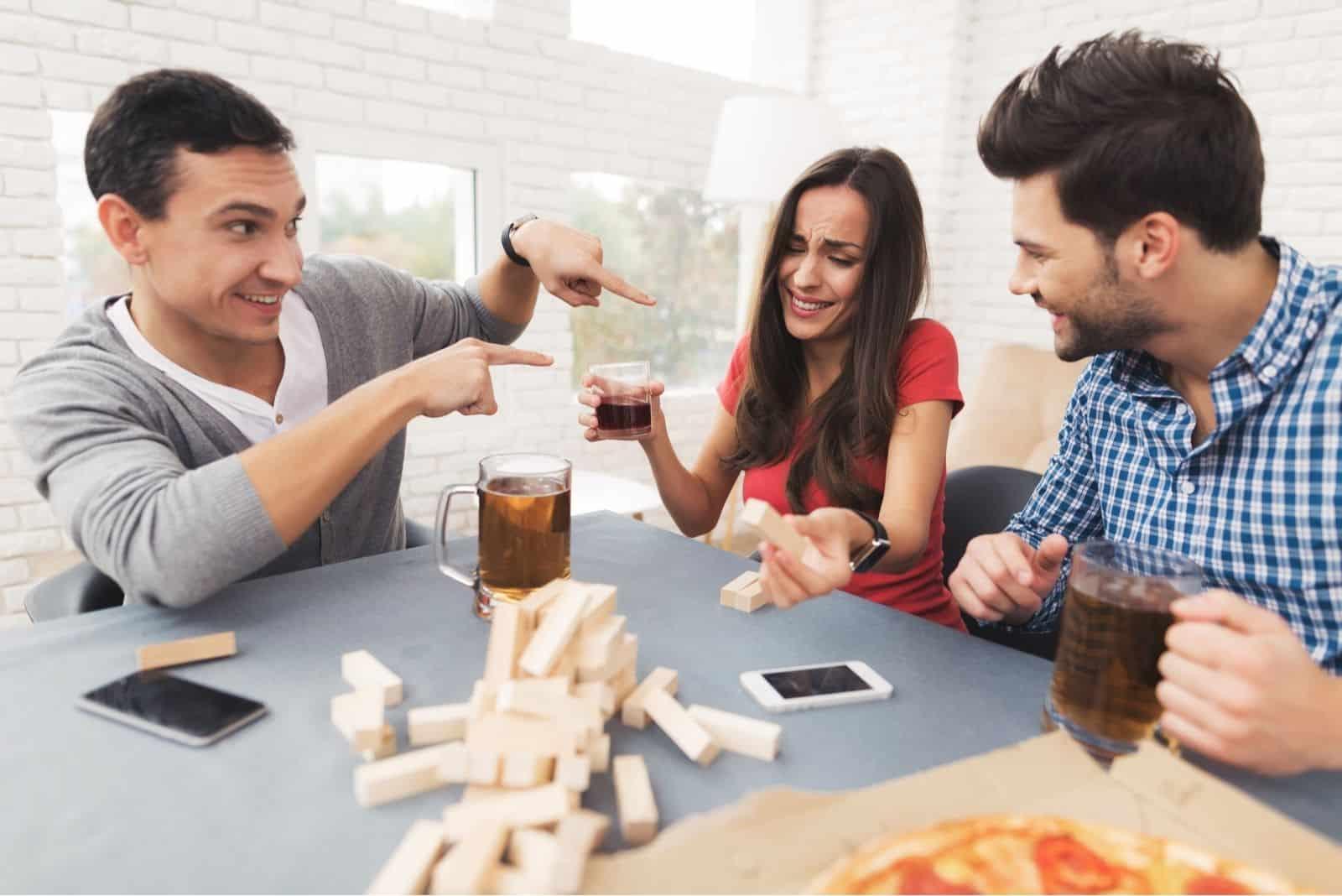 junge Leute spielen Jenga-Spiel mit Getränken und sie haben Spaß