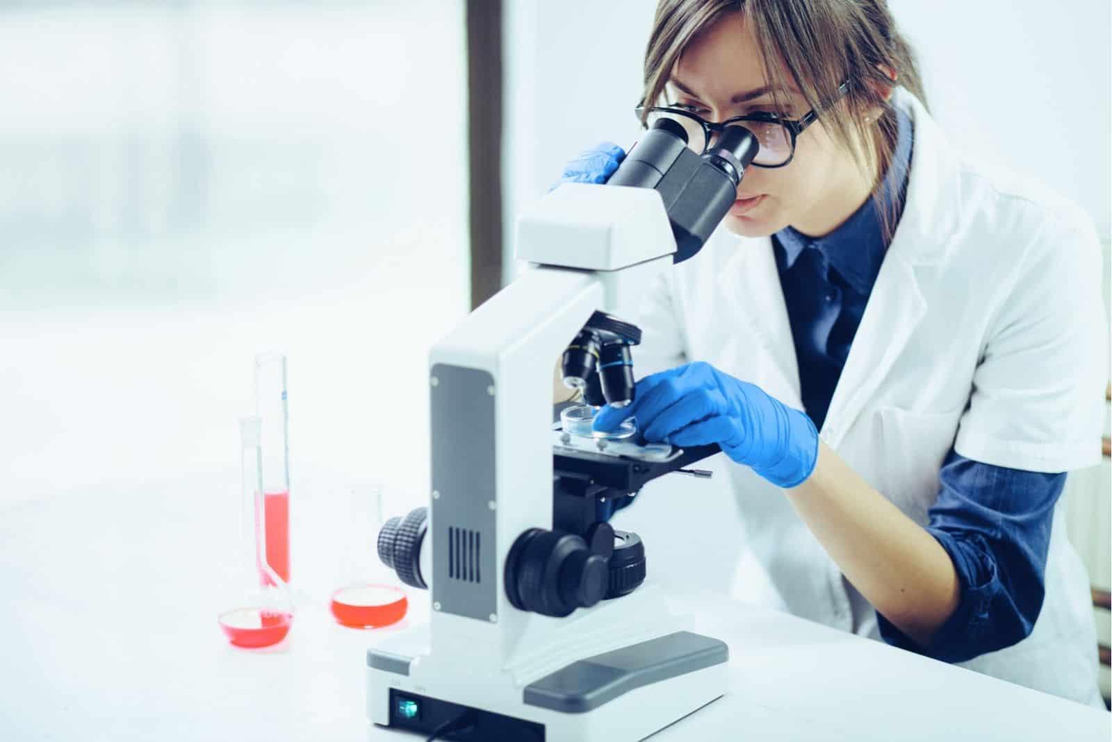 junge Wissenschaftlerin Blick durch ein Mikroskop im Labor