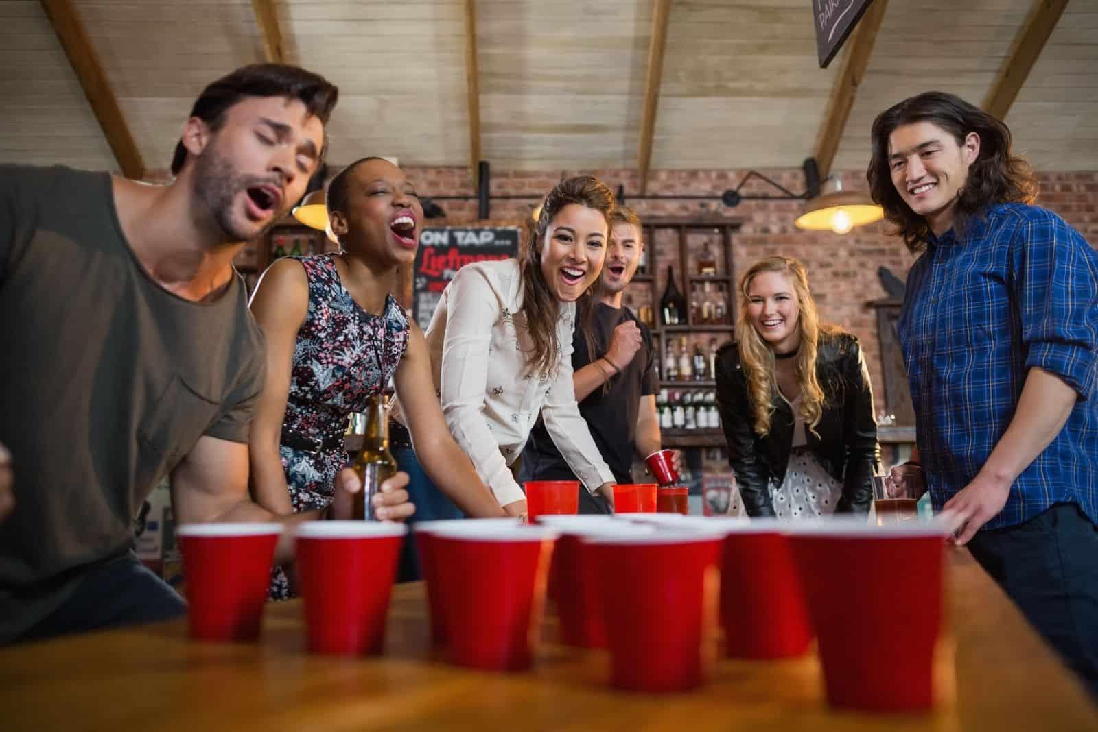 Junge Freunde spielen drinnen Bierpong
