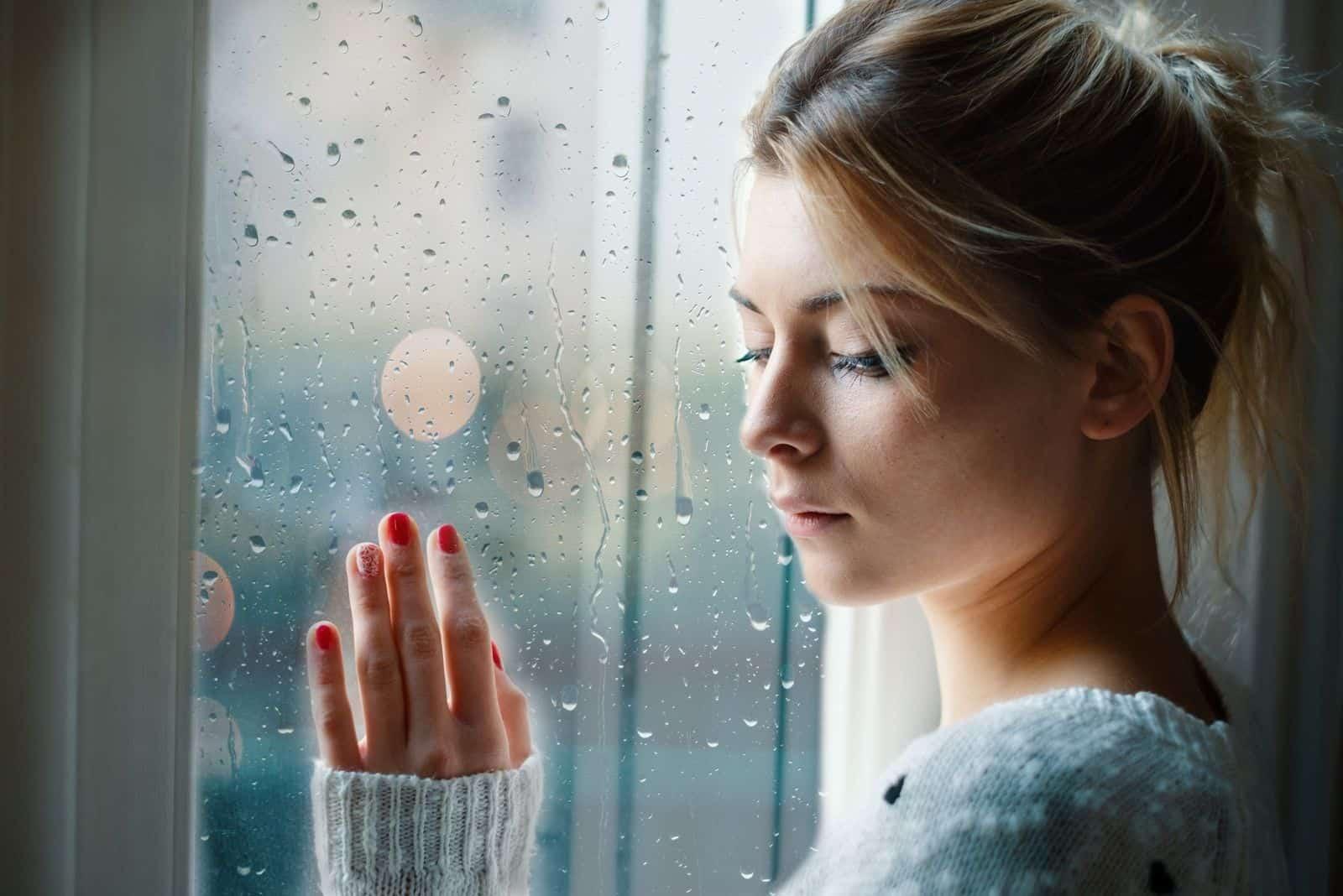 junge traurige frau mit Regentropfen vor den Fenstern