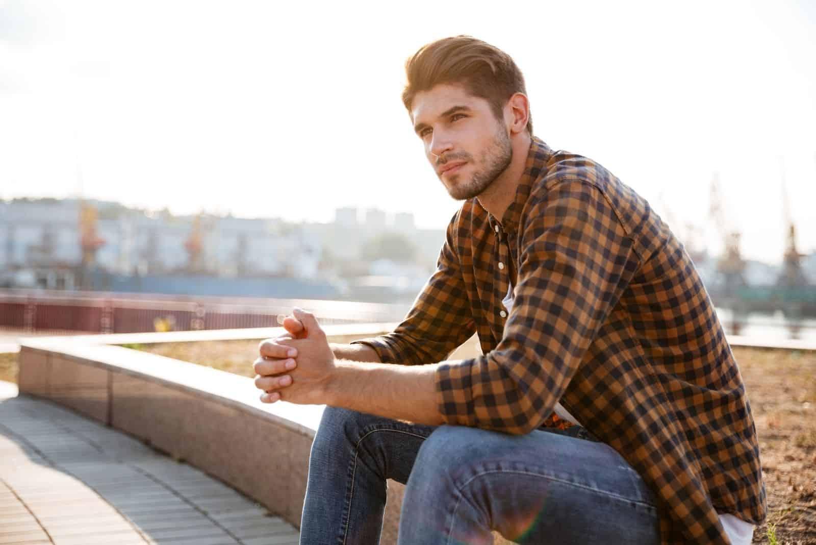 junger Mann denkt tief nach, während er auf der Straße sitzt