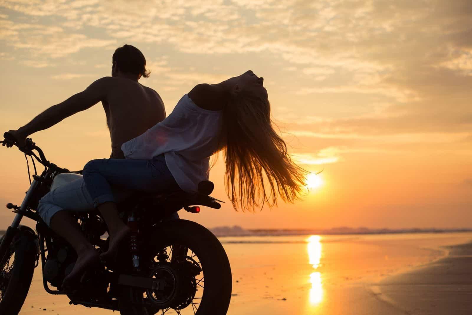 junges schönes Paar Hipster in stylischer Kleidung für ein Retro-Motorrad auf der Straße