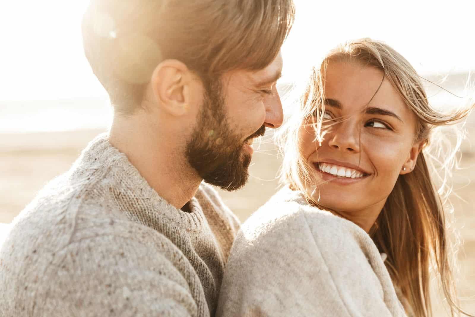lächelndes schönes junges Paar Umarmung beim Stehen am Strand in Nahaufnahme