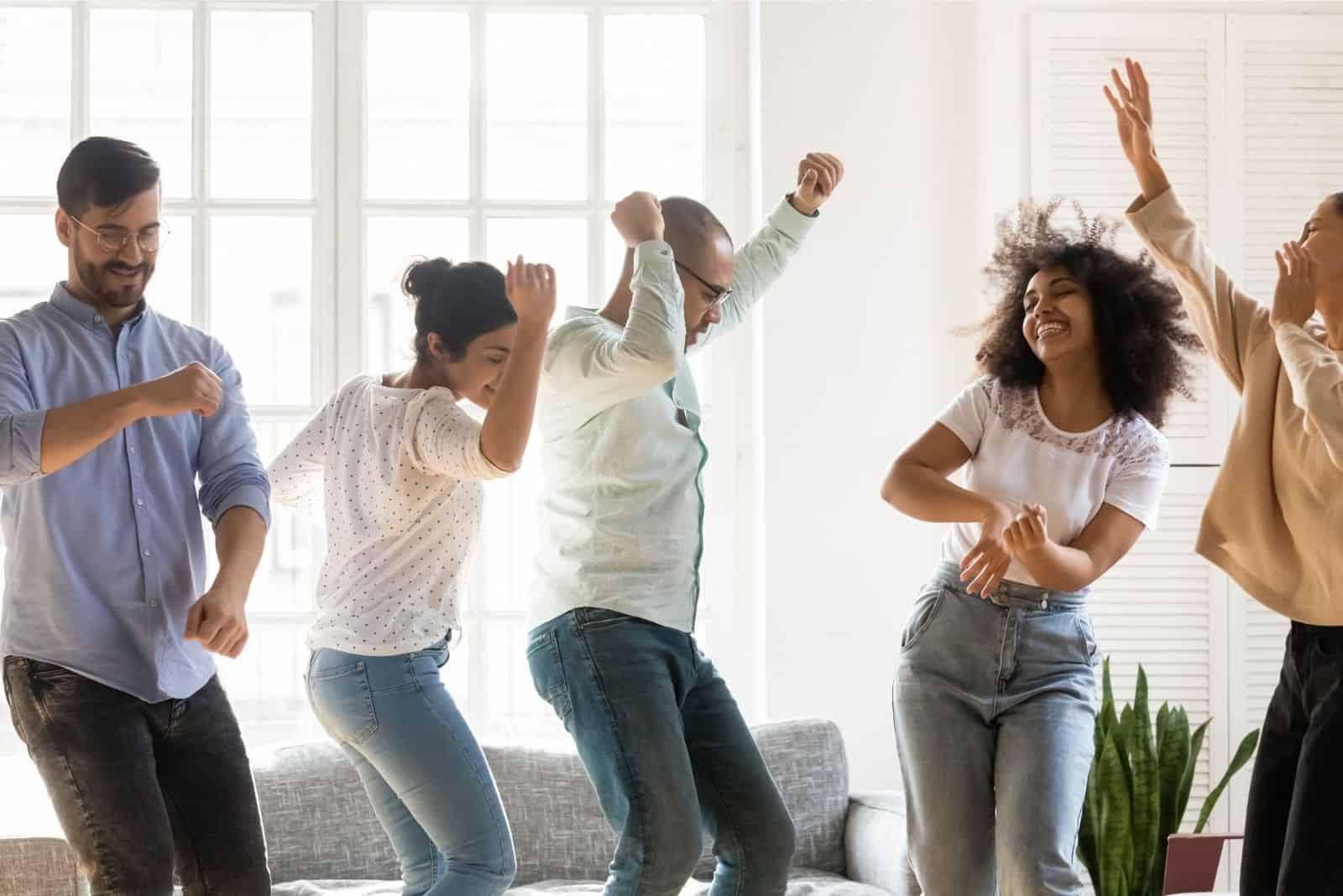 multinationale fröhliche Freunde tanzen und ähnliche Bewegungen drinnen machen