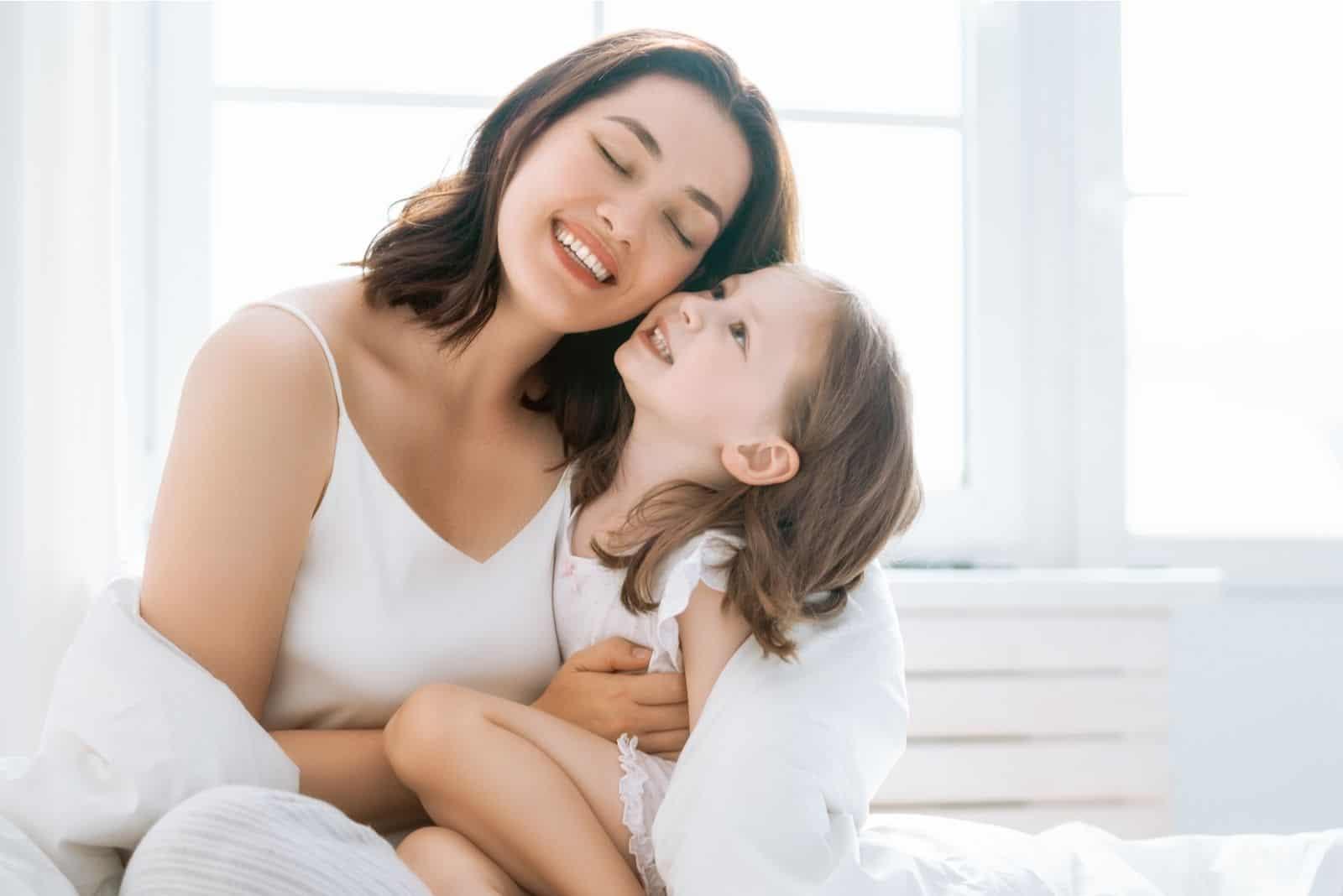 nettes Mädchen und Mutter den sonnigen Morgen im Schlafzimmer genießen