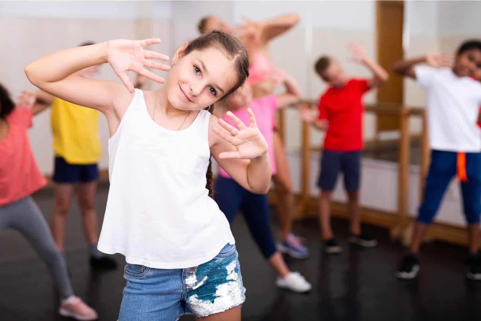 sportliches 10-jähriges Mädchen Übungsbewegungen von kräftigem Tanz während des Gruppenunterrichts in der Tanzschule