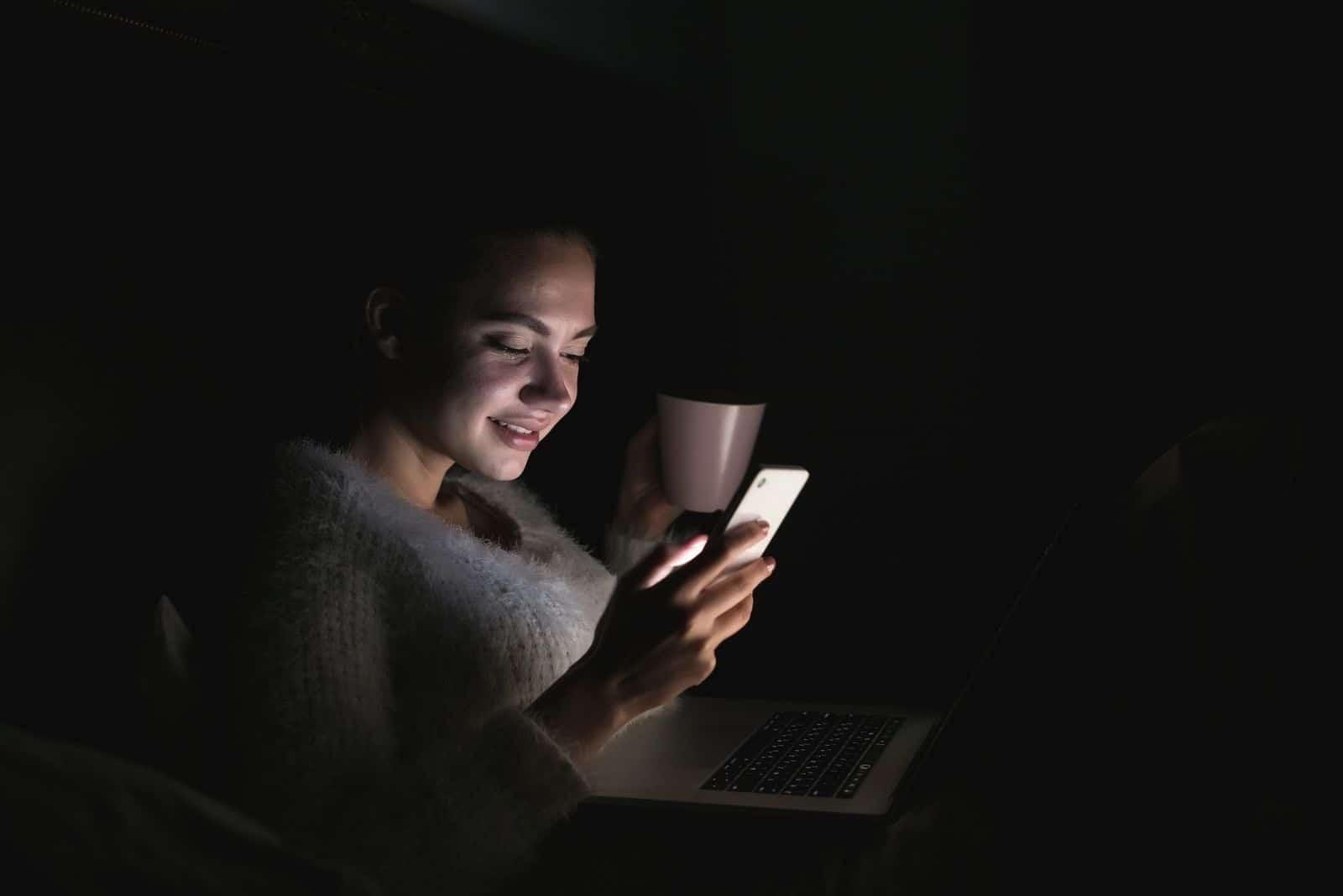 süßes junges Mädchen Nachts im Bett sitzen, mit Laptop, Tee trinken und aufs Telefon schauen, lächeln