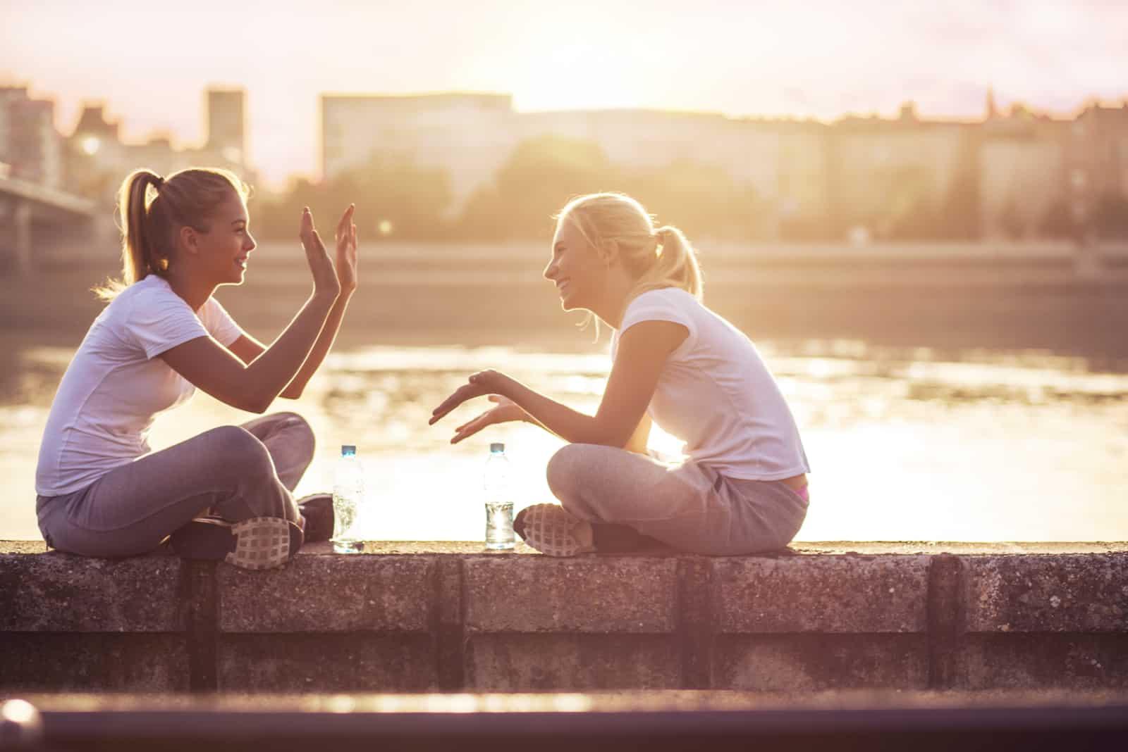 zwei freunde sitzen an der wand