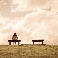 Frau sitzt allein auf einer Bank