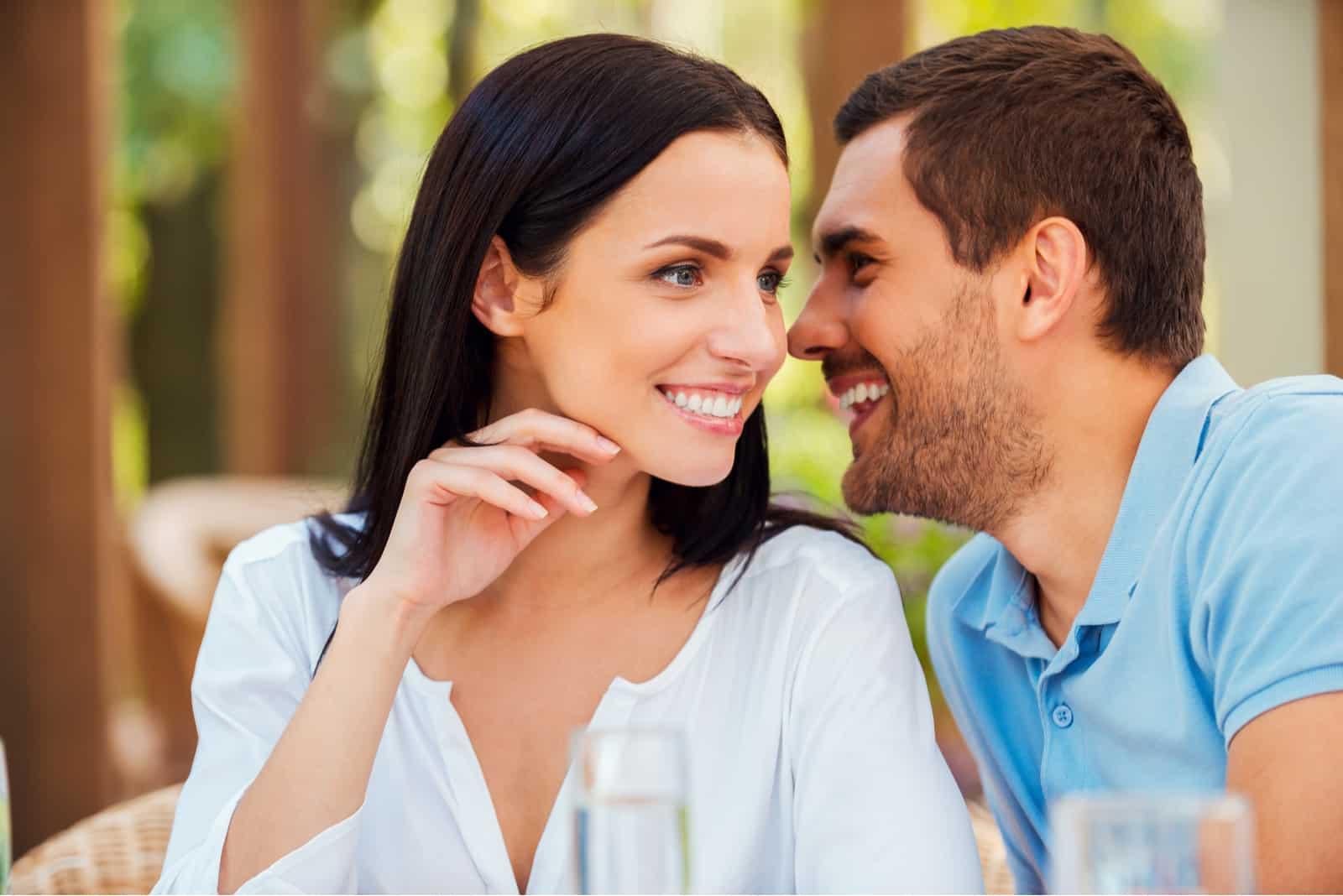 Der Mann flüstert der lächelnden Frau etwas zu