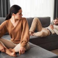 Frau dreht sich um und sieht den Mann auf der Couch an