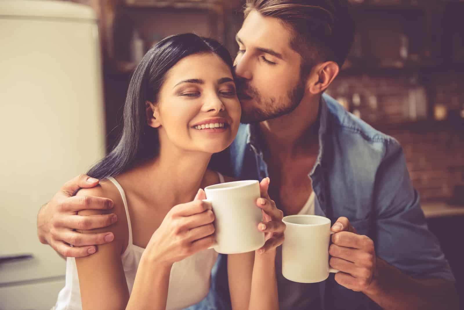 Ein Mann küsst eine Frau beim Kaffeetrinken auf die Stirn