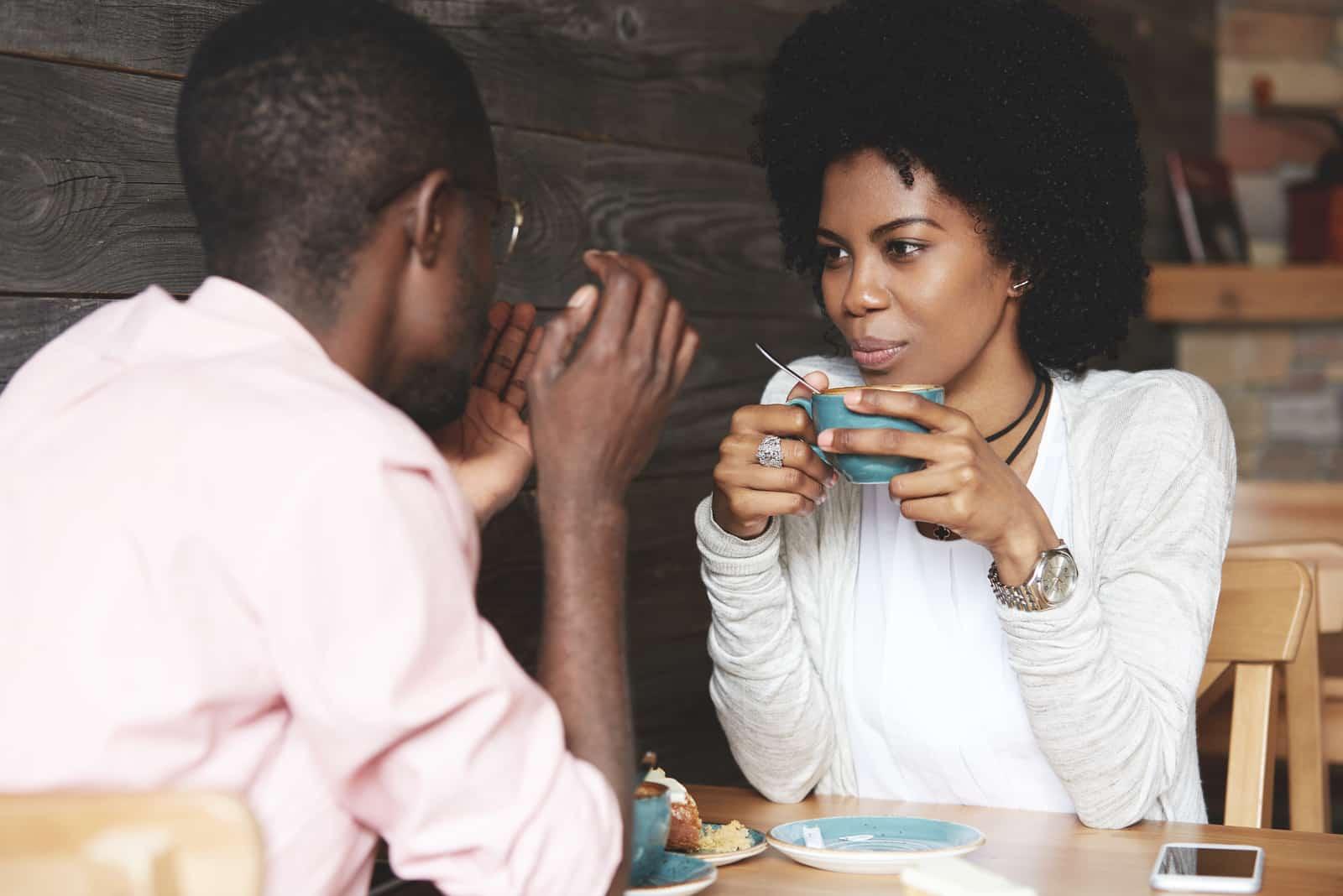 Frau, die eine Tasse Kaffee hält, zuhört und ihren Freund ansieht