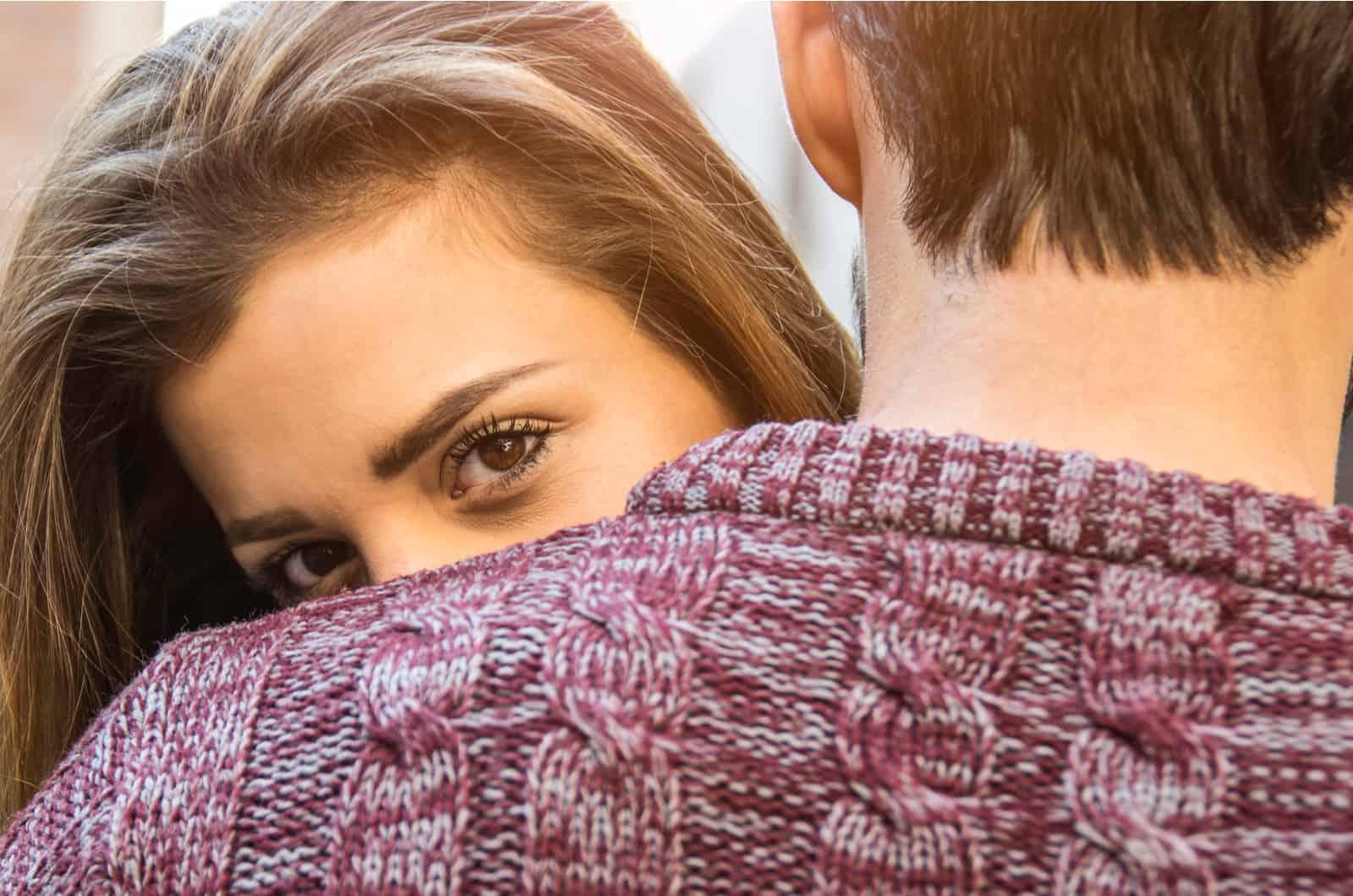 Frau schaut dem Mann über die Schulter in die Kamera