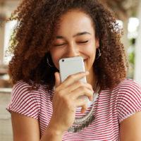 Frau, die ein Telefon hält und lacht