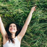 lächelnde junge Frau, die im Gras liegt