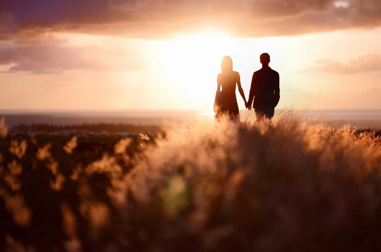 Paar Händchen haltend und Sonnenuntergang genießen