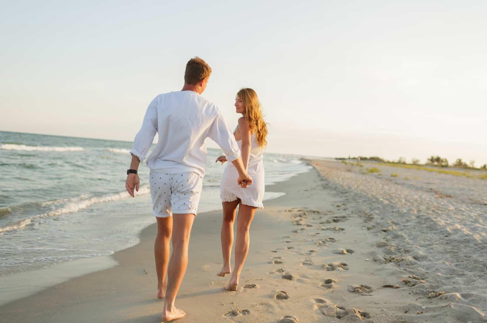 Paar am Strand spazieren und Händchen haltend