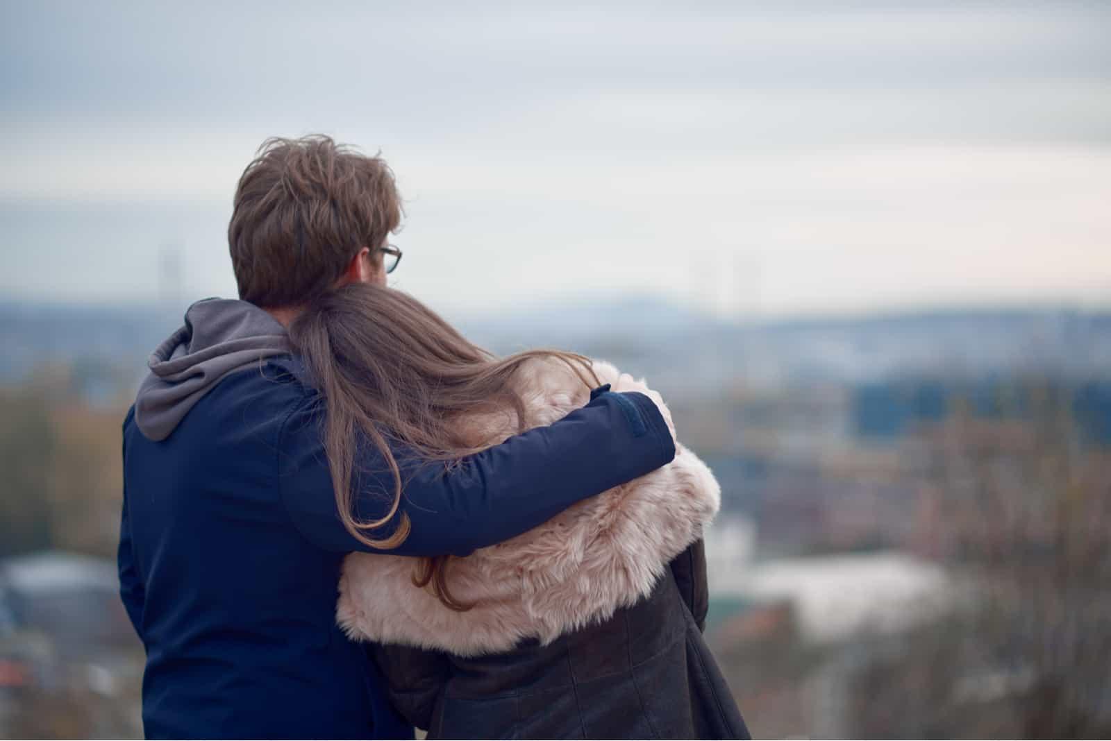 Paar umarmt und blickt auf den Horizont im Herbst