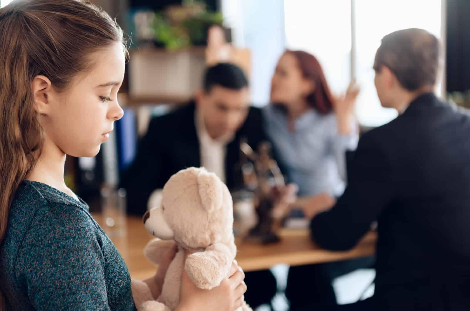 Tochter, die ihren Teddybär anschaut, während die Eltern im Hintergrund kämpfen