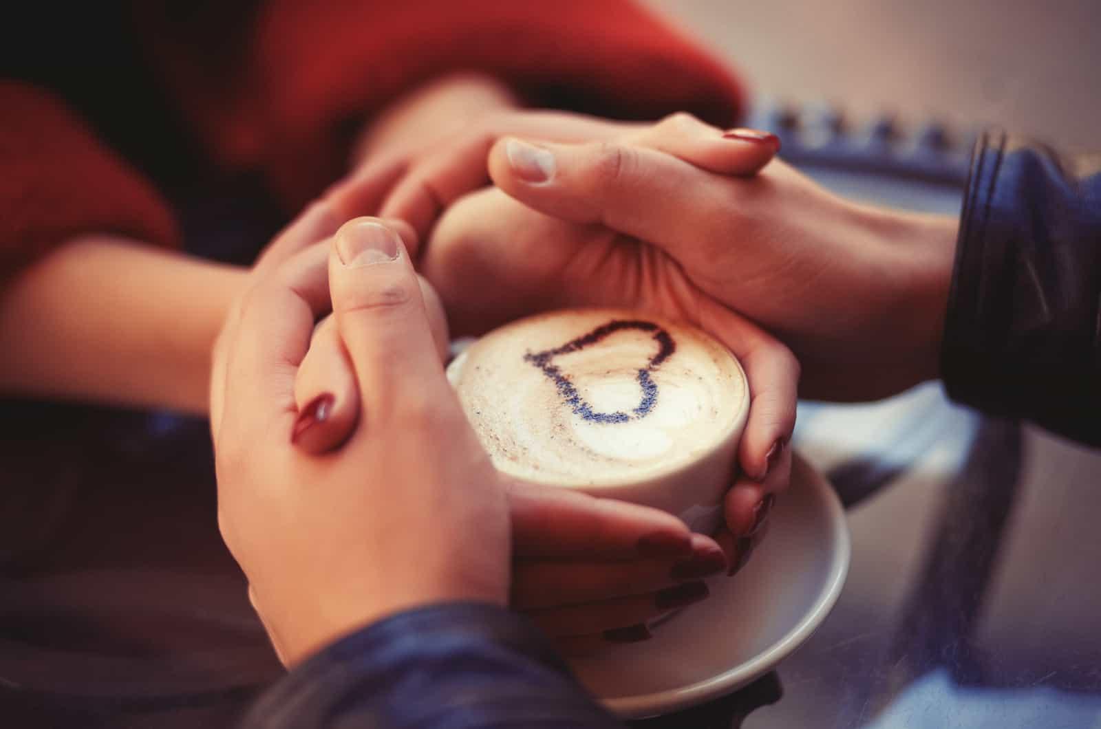 Vier Hände um eine Tasse Kaffee mit Herzzeichnung gewickelt