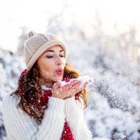 eine Frau mit einem Hut auf dem Kopf, die Schnee weht