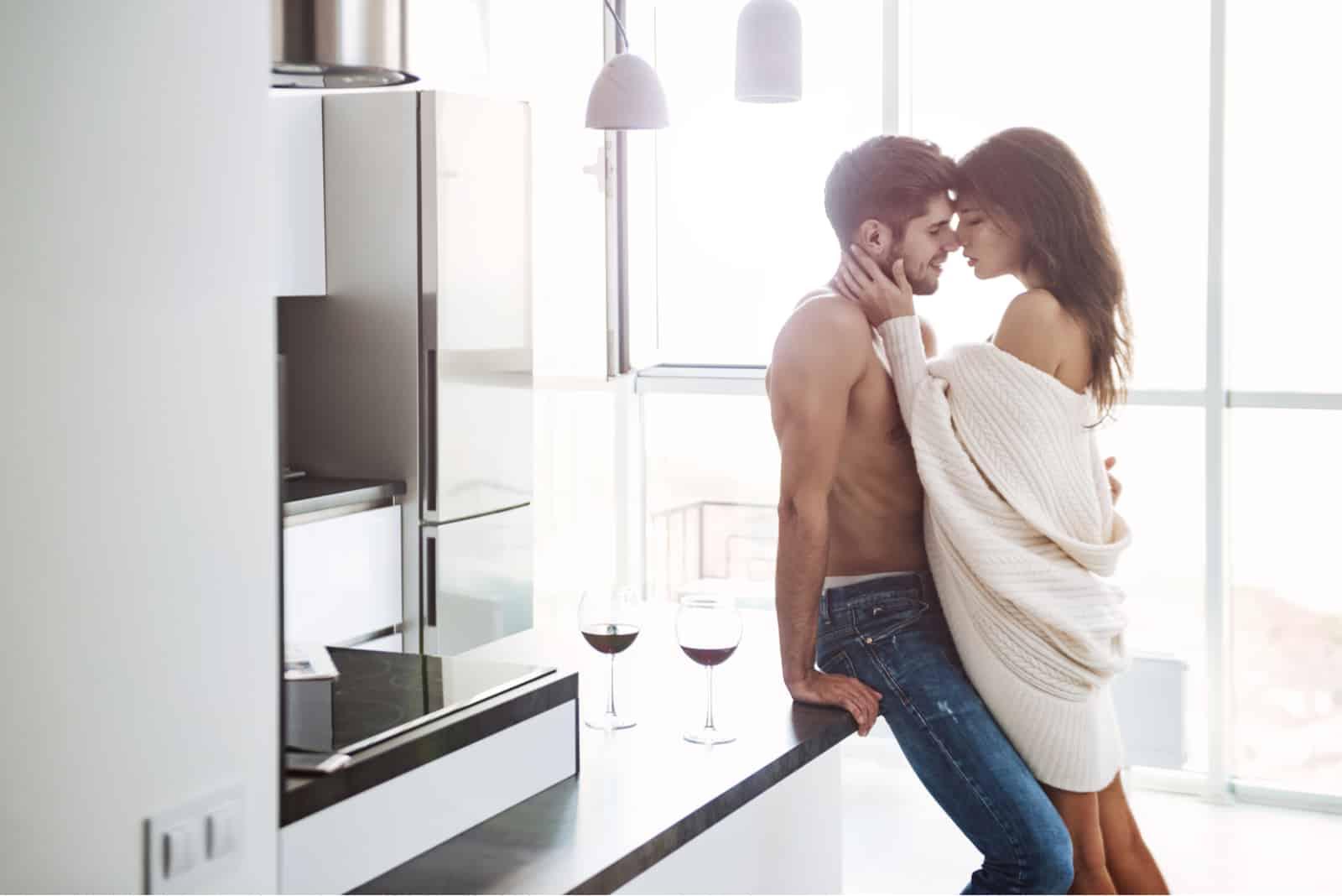 ein Mann und eine Frau, die sich in der Küche umarmen