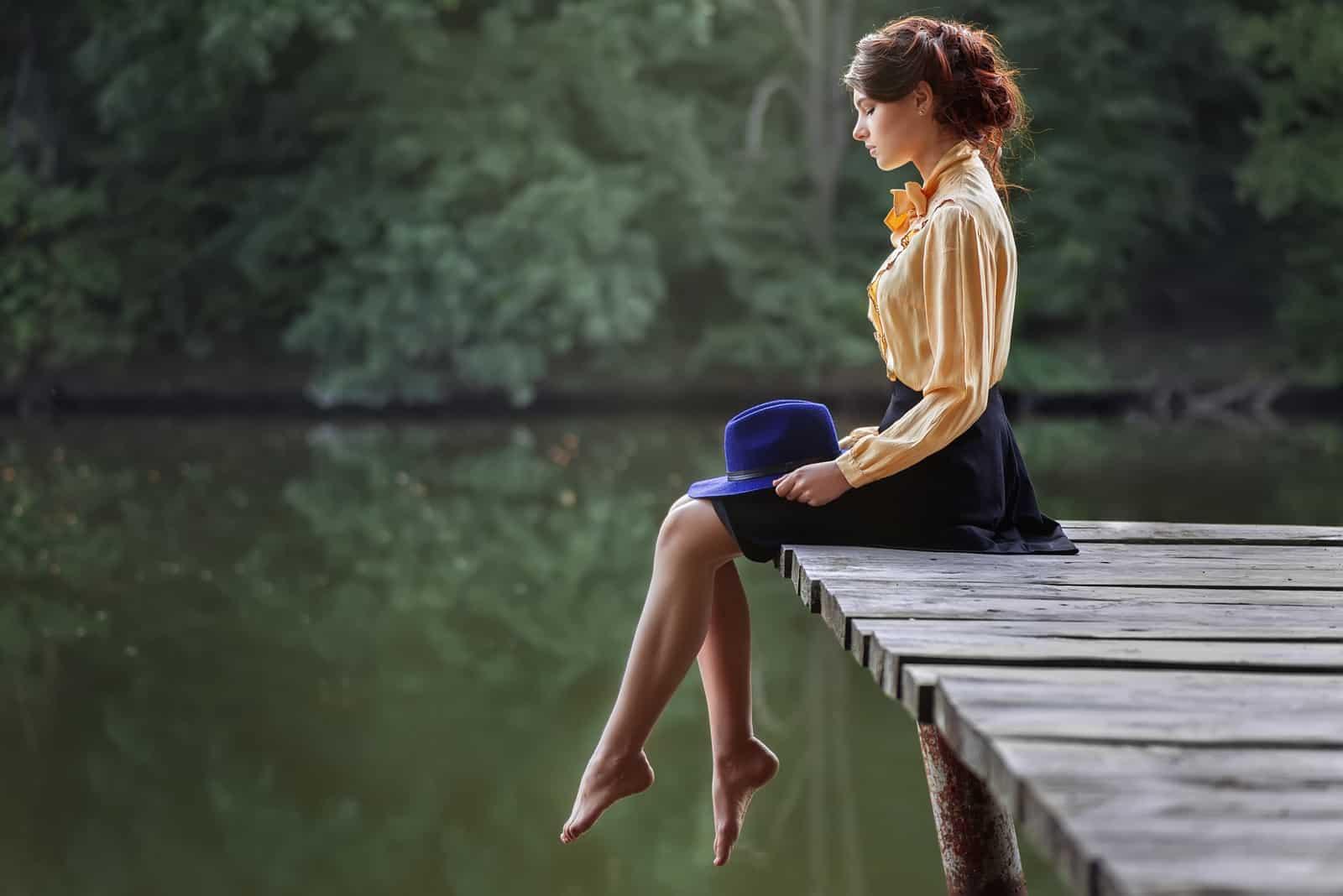 eine imaginäre Frau, die auf einem Pier sitzt