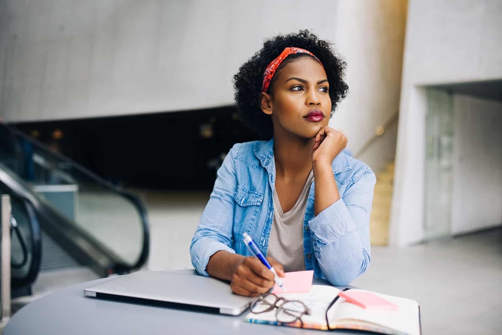 eine imaginäre Frau mit krausem Haar sitzt an einem Tisch und schreibt
