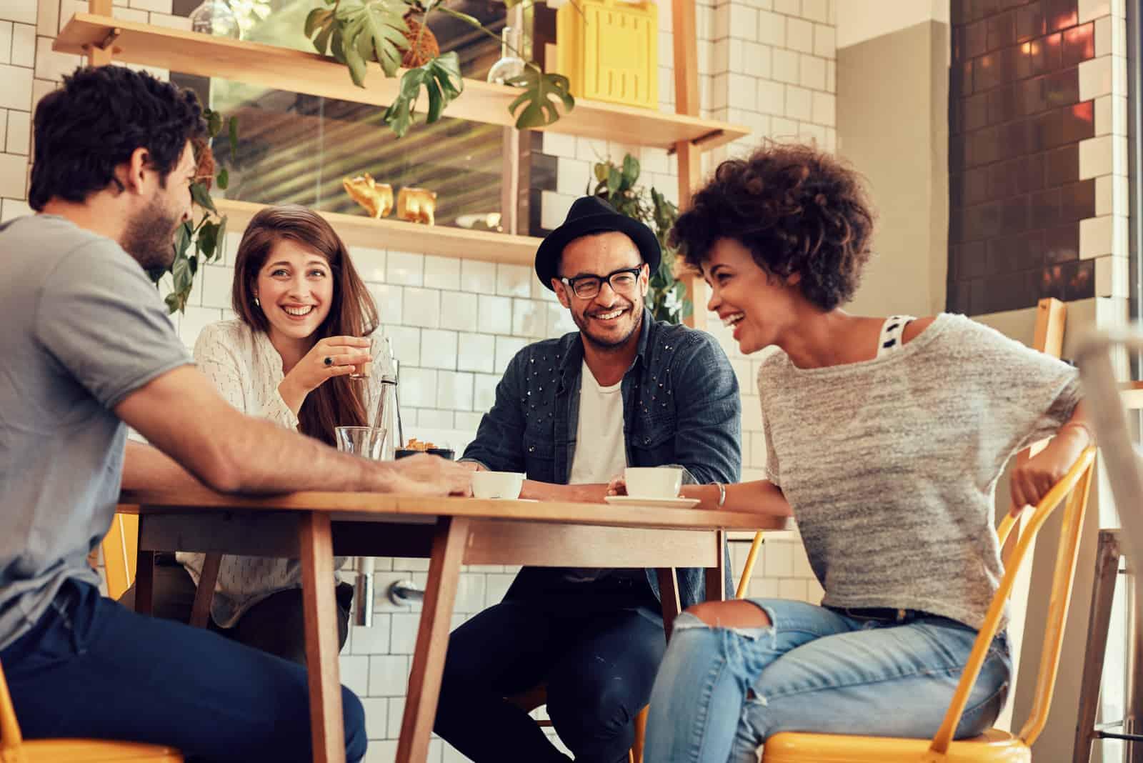 eine lächelnde Frau, die mit Freunden an einem Tisch sitzt