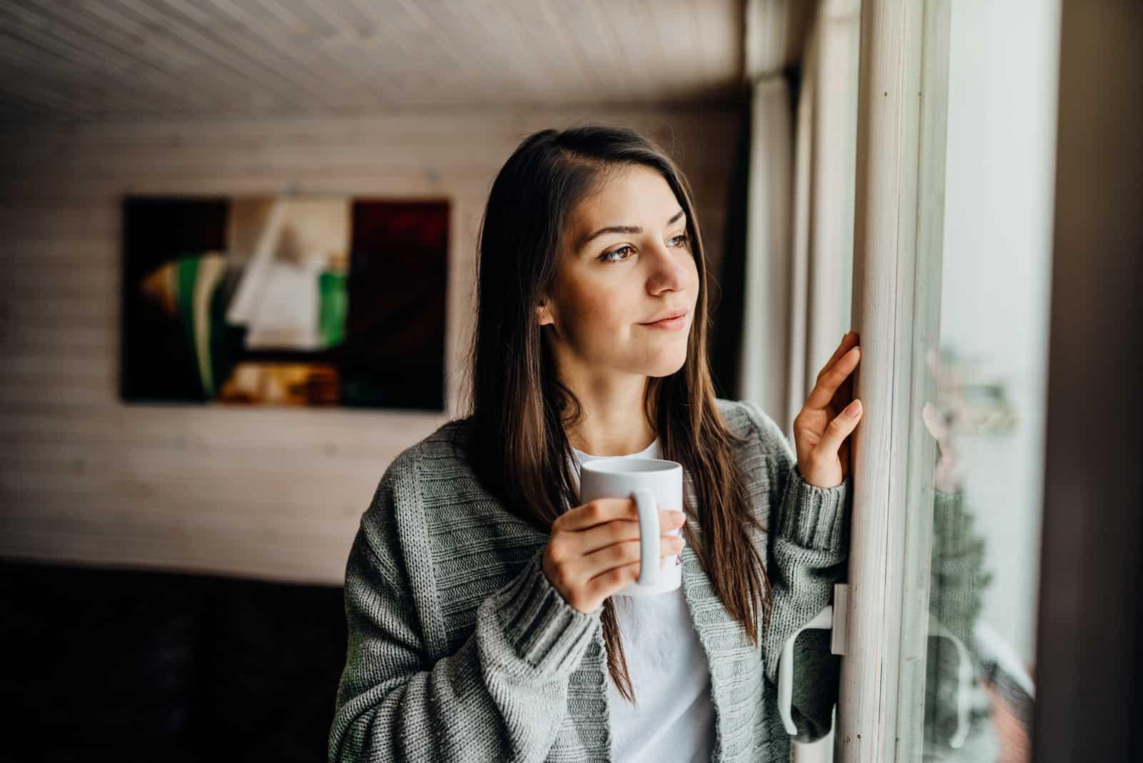 eine schwarzhaarige frau steht mit einer tasse kaffee am fenster