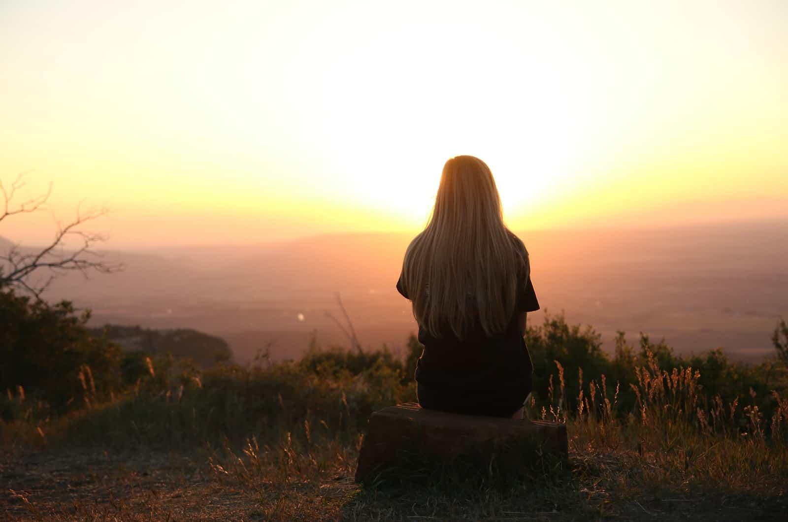 einsame frau beobachtet den sonnenuntergang