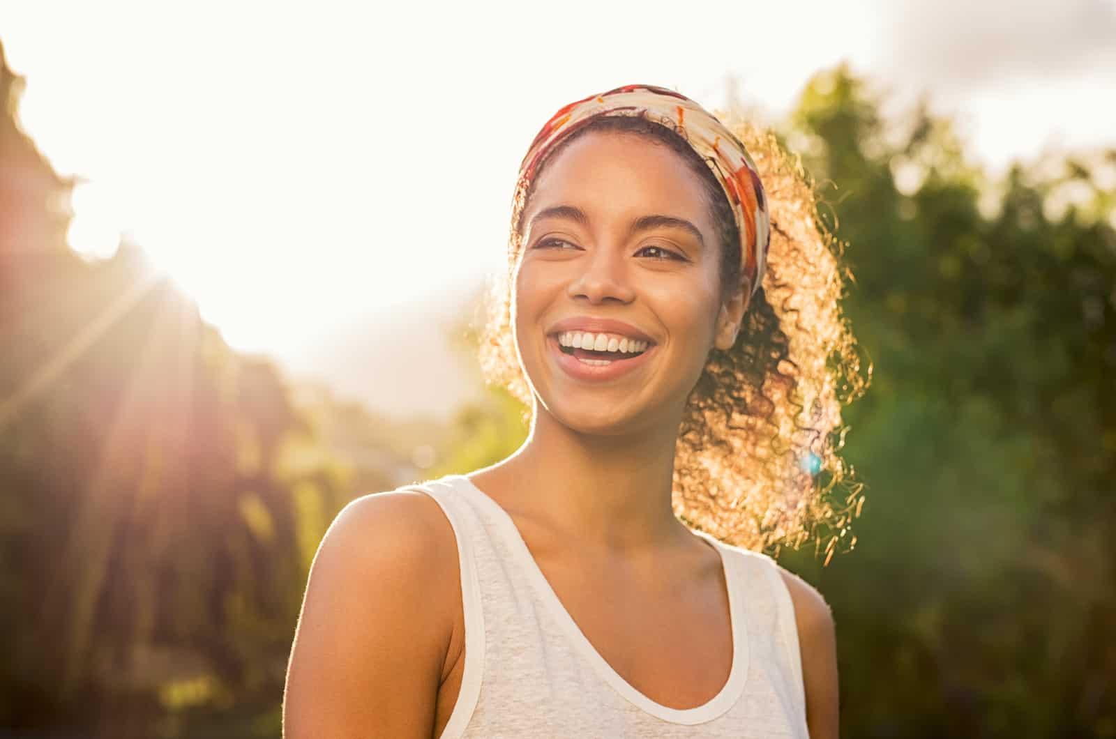 junge schöne Frau, die mit Sonnenuntergang im Hintergrund lächelt