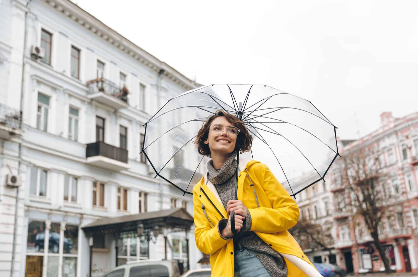 lachelnde junge frau in einem gelben regenmantel und einem regenschirm
