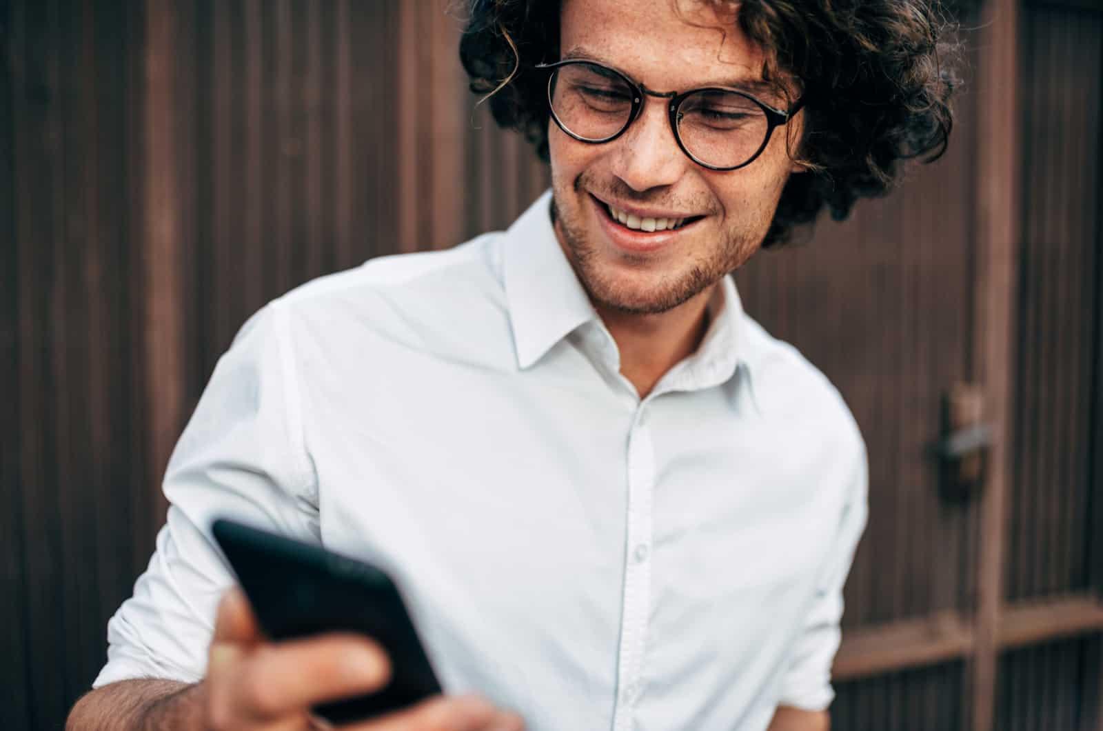 mann schaut auf telefon und lachelt