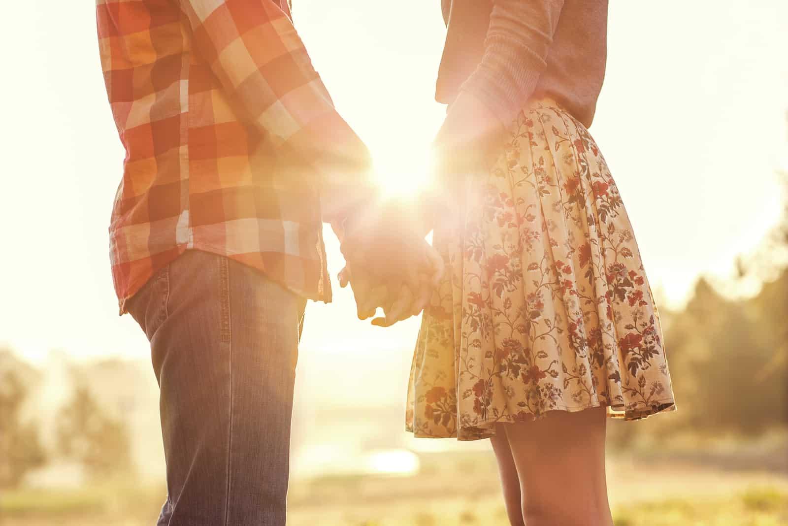 verliebtes Paar, das Händchen haltend im Herbstpark spazieren geht